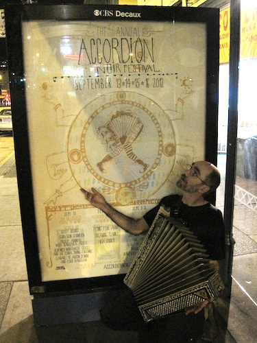 Picture of Bruce with an antique accordion in front of one of the Accordion Noir Festival bus shelter posters.